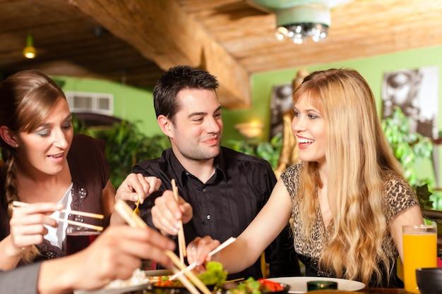 Jovens comendo no restaurante tailandês