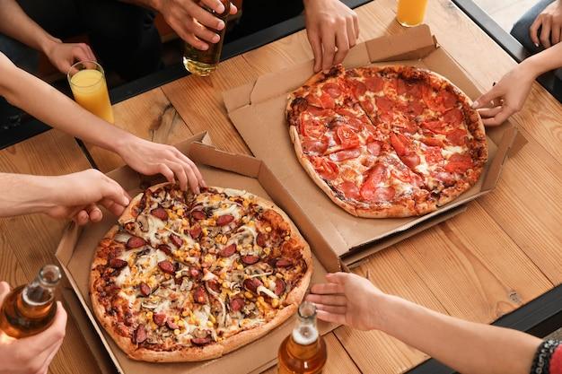 Jovens comendo pizza deliciosa na mesa, closeup