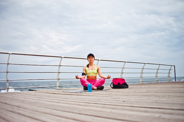 Jovens concentraram mulher sentada em um tapete de ioga em pose de lótus na praia