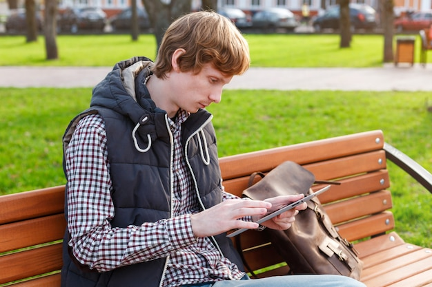 Jovens concentraram o homem com uma mochila, sentado no parque no banco e segurando um tablet
