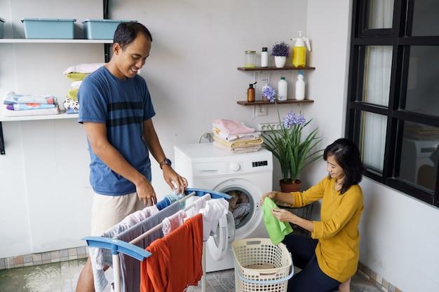 Jovens cônjuges asiáticos positivos lavando roupa regularmente e sorrindo juntos em casa