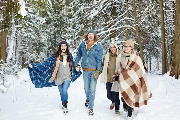 Jovens correndo na floresta de inverno