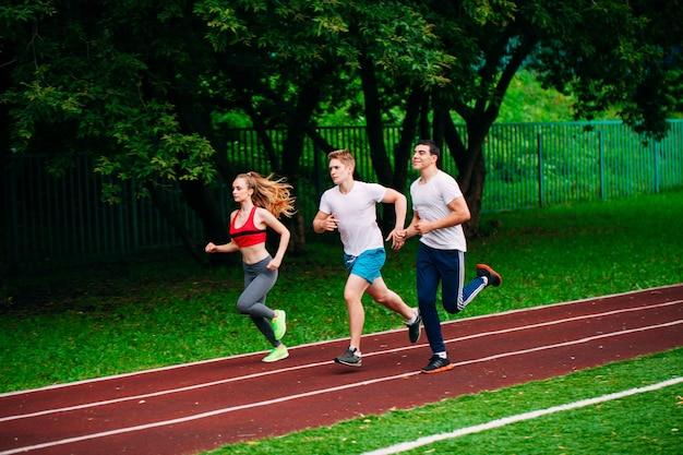 Jovens correndo na pista do estádio