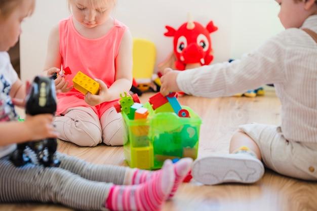 Jovens crianças sentadas no chão jogando
