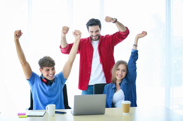 Jovens criativos alegres no sucesso no escritório