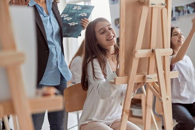 Jovens criativos e felizes alunos na sala de aula moderna estão fazendo aulas de desenho