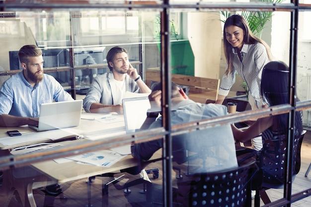 Jovens criativos em um escritório moderno, trabalhando em conjunto com laptop, tablet, smartphone, notebook