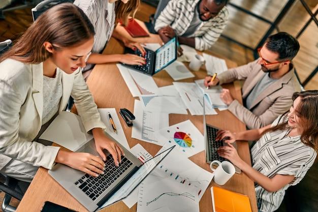 Jovens criativos multirraciais em um escritório moderno. um grupo de jovens empresários está trabalhando junto com um laptop, smartphone. uma equipe de hipster de sucesso em um espaço de coworking.