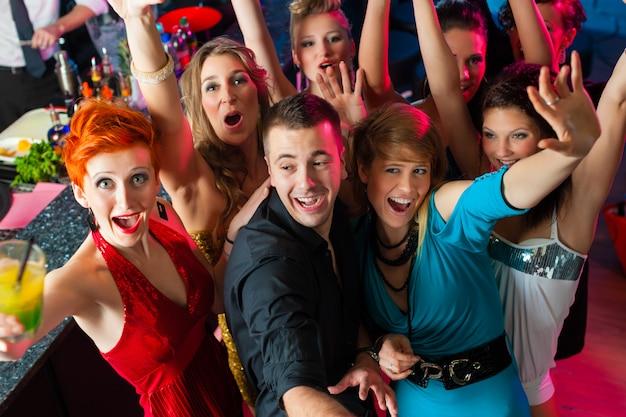 Jovens dançando no clube ou discoteca, homens e mulheres