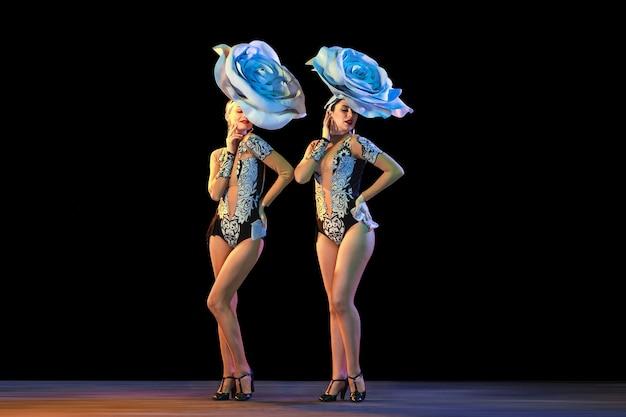 Jovens dançarinas com enormes chapéus florais em luz de néon na parede preta