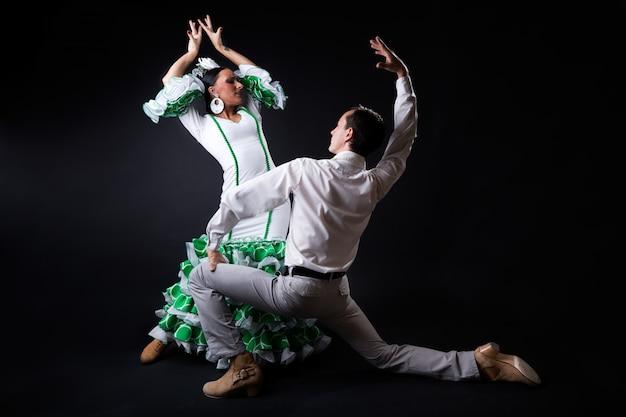 Jovens dançarinos de flamenco com lindo vestido no fundo preto.