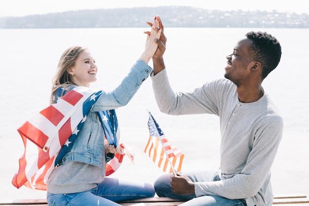 Jovens, dar, alto, cinco, enquanto, segurando, bandeira americana