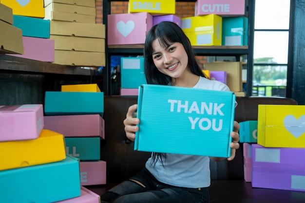 Jovens de compras on-line iniciam pequenos negócios em uma caixa de papelão no trabalho. o vendedor prepara a caixa de entrega para o cliente, vendas on-line ou comércio eletrônico., conceito de vendas.