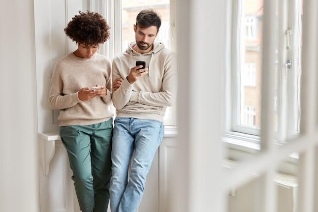 Jovens de diferentes raças usam aparelhos modernos para navegar na internet, ignoram a comunicação real