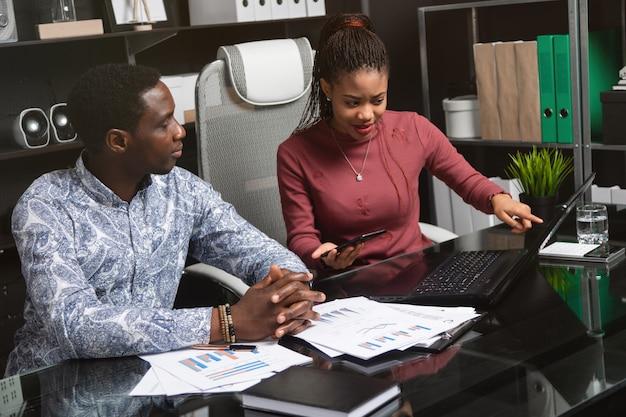 Jovens de negócios de nacionalidade afro-americana trabalhando com documentos e telefone