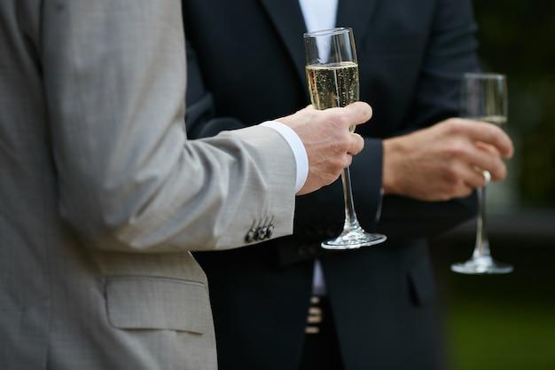Jovens de terno segurando uma taça de champanhe