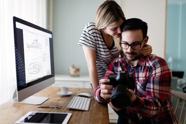 Jovens designers atraentes trabalhando juntos em casa