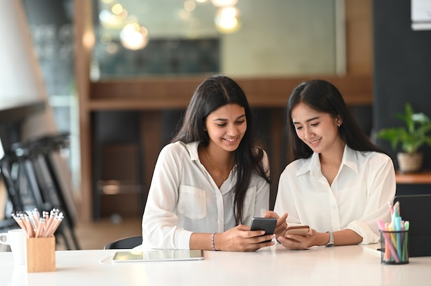 Jovens designers de interiores usando smartphone discutindo ideias para um novo projeto no escritório.