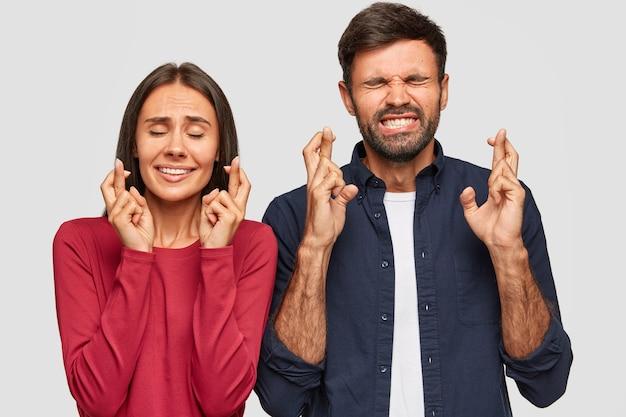 Jovens do sexo masculino e feminino fecham os olhos, cruzam os dedos de esperança, antecipam algo com expressões fiéis, têm sorrisos