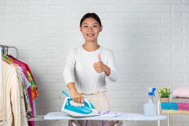 Jovens donas de casa que estão usando ferros passando as roupas em um tijolo branco.