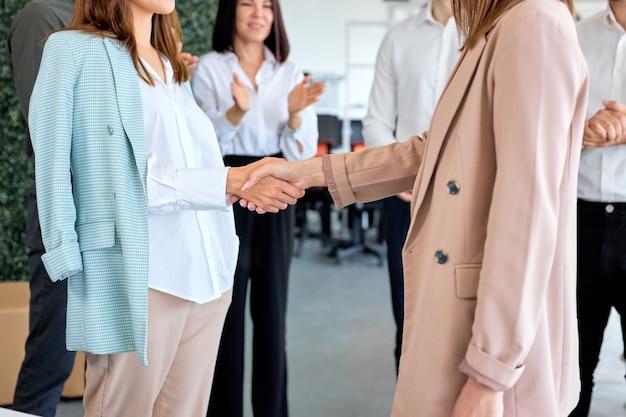 Jovens duas senhoras de negócios colhidas em roupa formal, apertando as mãos, terminando o contrato no escritório moderno e brilhante, na presença de colegas batendo palmas. aperto de mão e marketing. copie o espaço. vista lateral