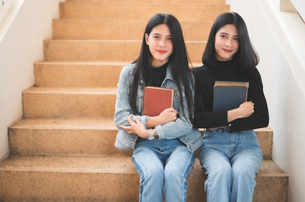 Jovens e belas estudantes têm livros para estudar na universidade.
