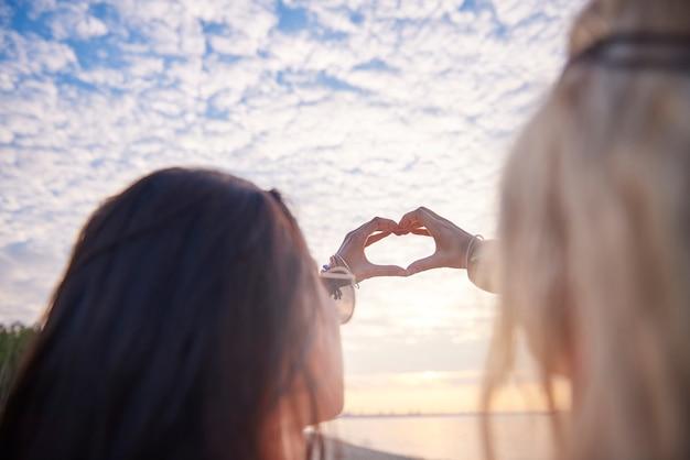 Jovens e belas mulheres fazendo um movimento de coração com as mãos