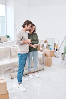 Jovens e felizes colonos amorosos de uma nova casa ou apartamento em pé no centro da sala de estar discutindo o esboço de um apartamento no tablet