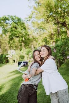 Jovens e lindas blogueiras influenciadoras sorridentes estão filmando ou gravando vídeos com seus smartphones em um estabilizador, em um parque verde ensolarado do lado de fora. conceito de blogging. foco seletivo suave.