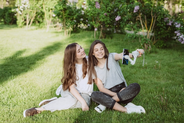 Jovens e lindas blogueiras influenciadoras sorridentes estão filmando ou gravando vídeos com seus telefones celulares em um estabilizador, em um parque verde ensolarado do lado de fora. conceito de blogging. foco seletivo suave.