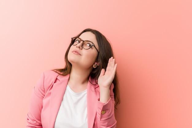 Jovens e mais mulher caucasiana de negócios de tamanho tentando ouvir uma fofoca.