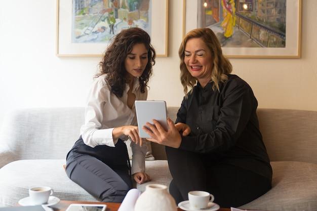 Jovens e mulheres de meia idade usando tablet juntos