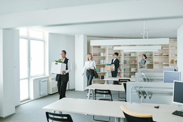 Jovens elegantes e felizes trabalhadores de colarinho branco voltando ao escritório após um período de auto-isolamento e quarentena causado pelo surto de covid19