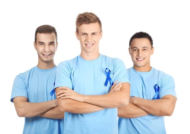 Jovens em camisetas com fitas azuis na superfície branca. conceito de conscientização do câncer de próstata