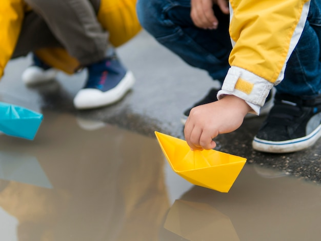 Jovens em capas de chuva brincando com barcos de plástico