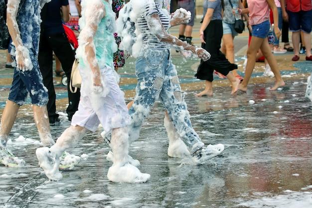 Jovens em espuma com sabão caminhando em uma estrada molhada