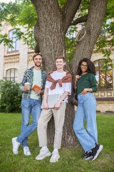 Jovens em pé perto da árvore no parque