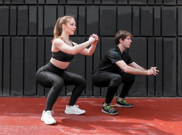 Jovens em roupas esportivas se exercitando ao ar livre