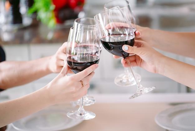 Jovens em um restaurante bebendo vinho no fundo um cozinheiro prepara.