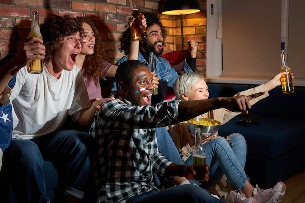 Jovens empolgados assistindo jogos esportivos, campeonatos em casa, torcendo pelo basquete, tênis, futebol, time de hóquei nacional favorito. conceito de emoções.