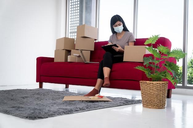 Jovens empreendedores asiáticos felizes com uma máscara arrumando caixas para entrega de produtos