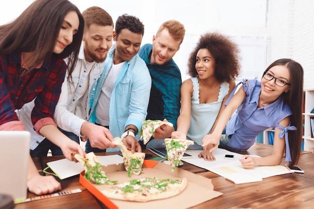 Jovens empregados comem pizza juntos.