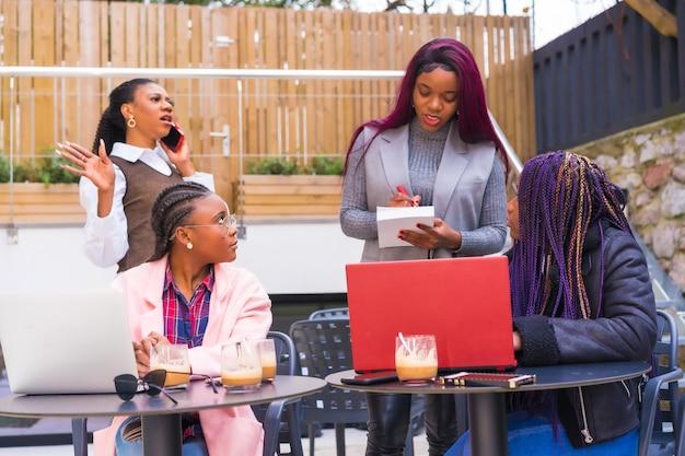 Jovens empresárias de etnia negra. em uma reunião de negócios em uma cafeteria com computadores e falando ao telefone