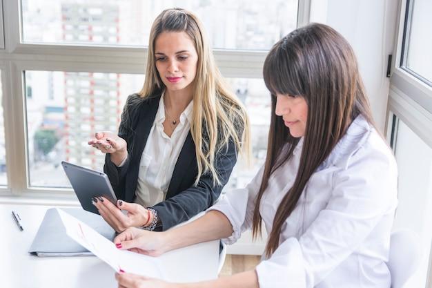 Jovens empresárias discutindo documento no escritório