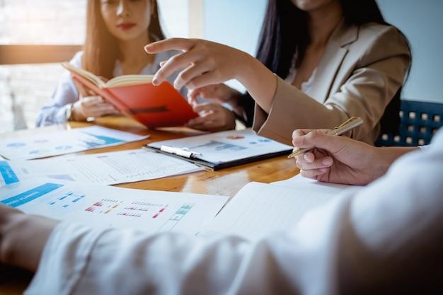 Jovens empresárias discutir a estratégia de gráficos e plano financeiro