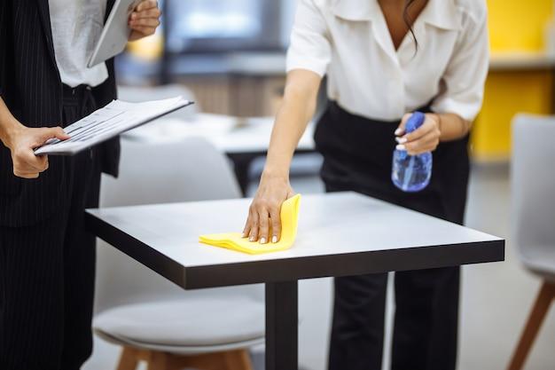 Jovens empresárias limpam o local de trabalho, limpam a mesa com um pano amarelo.
