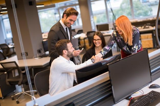 Jovens empresários apertando as mãos no escritório