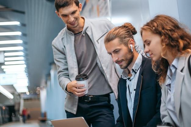 Jovens empresários com laptop na plataforma do metrô