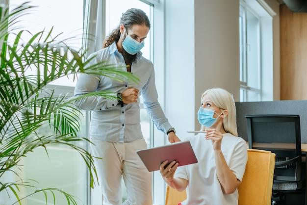 Jovens empresários com máscaras médicas protetoras discutindo algo no escritório