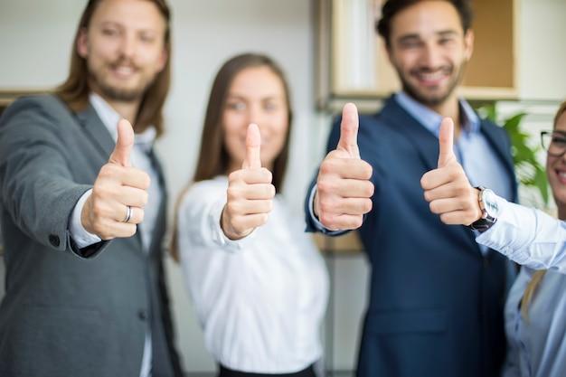 Jovens empresários com o polegar para cima em pé no escritório
